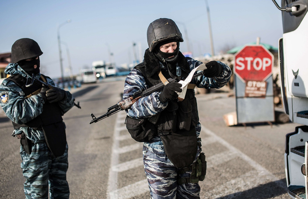 . A pro-Russian serviceman checks a driver\'s documents at Chongar checkpoint blocking the entrance to Crimea on March 10, 2014. Russia vowed on March 10 to unveil its own solution to the Ukrainian crisis that would run counter to US efforts and would appear to leave room for Crimea to switch over to Kremlin rule. The unexpected announcement came as Ukraine\'s new pro-European leaders raced to rally Western support in the face of the seizure by Kremlin-backed forces of the strategic Black Sea peninsula and plans to hold a Sunday referendum on switching Crimea\'s allegiance from Kiev to Moscow. ALISA BOROVIKOVA/AFP/Getty Images