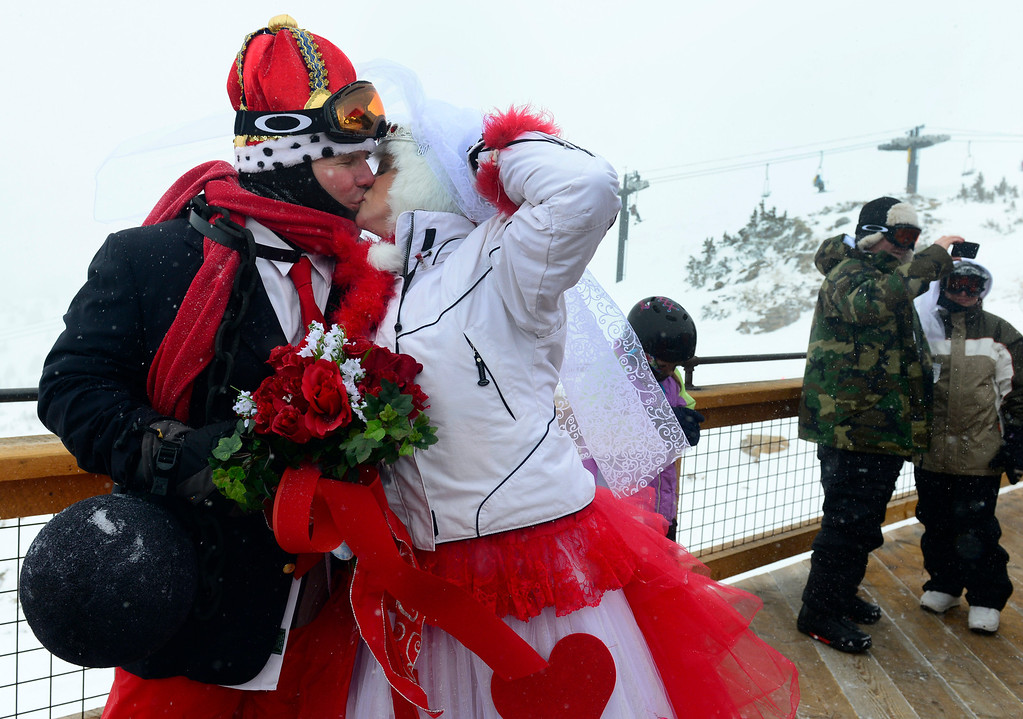 """. GEORGETOWN, CO - FEBRUARY 14: Dave Sitarski and his bride Kris Slager from Evergreen share a kiss before the start of the ceremony. Dozens of couples decided to say \""""I do\"""" for the first time or repeat their wedding vows on Valentines Day at the 23rd Annual Mountaintop Matrimony at Loveland Basin ski area. The couples hovered together to keep warm with white-out conditions at 12, 050 feet just outside the Ptarmagin Roost cabin at the top of chairlift #2 with the minister Harry Heilman officiating. (Photo by Kathryn Scott Osler/The Denver Post)"""