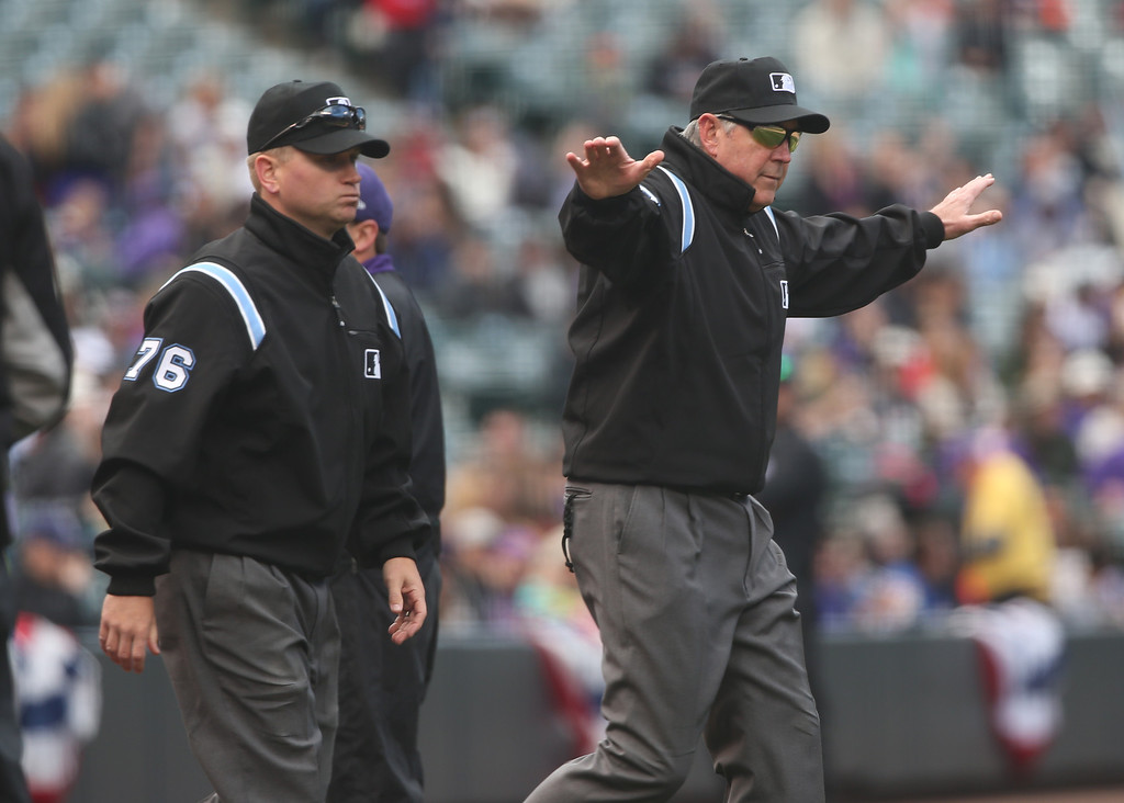 . Crew chief Mike Winters, right, signals safe as first base umpire Mike Muchlinski looks on after a video replay to check if Colorado Rockies\' leadoff hitter Charlie Blackmon slid safely into first base for a single against the Arizona Diamondbacks in the first inning of an MLB National League baseball game in Denver on Sunday, April 6, 2014. (AP Photo/David Zalubowski)