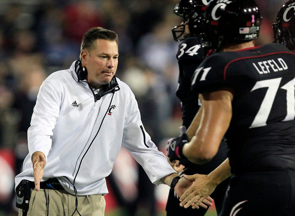 . FILE - In this Oct. 13, 2012, file photo, Cincinnati head coach Butch Jones, left, slaps hands with his players as they run off the field after scoring a touchdown in the second half of an NCAA college football game against Fordham in Cincinnati. The bowl-bound Bearcats wait to hear from coach Jones about whether he\'ll stay or head off to either Purdue or Colorado. (AP Photo/Al Behrman, File)