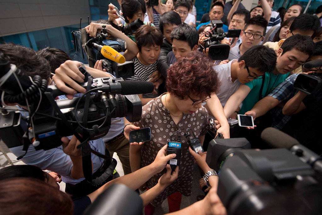 . A woman (C), believed to be the mother of a victim of an Asiana Airlines aircraft crash in San Francisco, is surrounded by members of the media in the lobby of the company\'s headquarters in Seoul on July 7, 2013. At least two people were killed and 130 injured when an Asiana Airlines Boeing 777 jet crashed and caught fire as it landed short of the runway at San Francisco International Airport.  Ed Jones/AFP/Getty Images