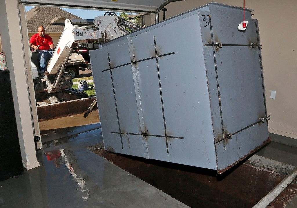 . In this Friday, May 2, 2014 photo, Art Munoz, of GFS Storm Shelters, maneuvers a storm shelter into a garage at a residence in Yukon, Okla.  (AP Photo/Sue Ogrocki)