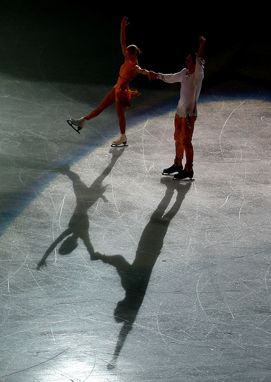 . Gold medalists Tatiana Volosozhar and Maxim Trankov of Russia skate toward the podium during the flower ceremony for the Figure Skating Pairs event during day five of the 2014 Sochi Olympics at Iceberg Skating Palace on February 12, 2014 in Sochi, Russia.  (Photo by Clive Mason/Getty Images)