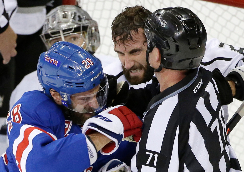 . New York Rangers center Dominic Moore (28), scuffles with Los Angeles Kings center Jarret Stoll as linesman Brad Kovachik (71) steps in to break it up in the first period during Game 4 of the NHL hockey Stanley Cup Final, Wednesday, June 11, 2014, in New York. (AP Photo/Frank Franklin II)