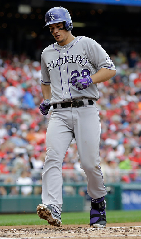 . Colorado Rockies\' Nolan Arenado crosses home plate to score after hitting a solo home run during the fourth inning of a baseball game against the Washington Nationals at Nationals Park, Sunday, June 23, 2013, in Washington. (AP Photo/Carolyn Kaster)