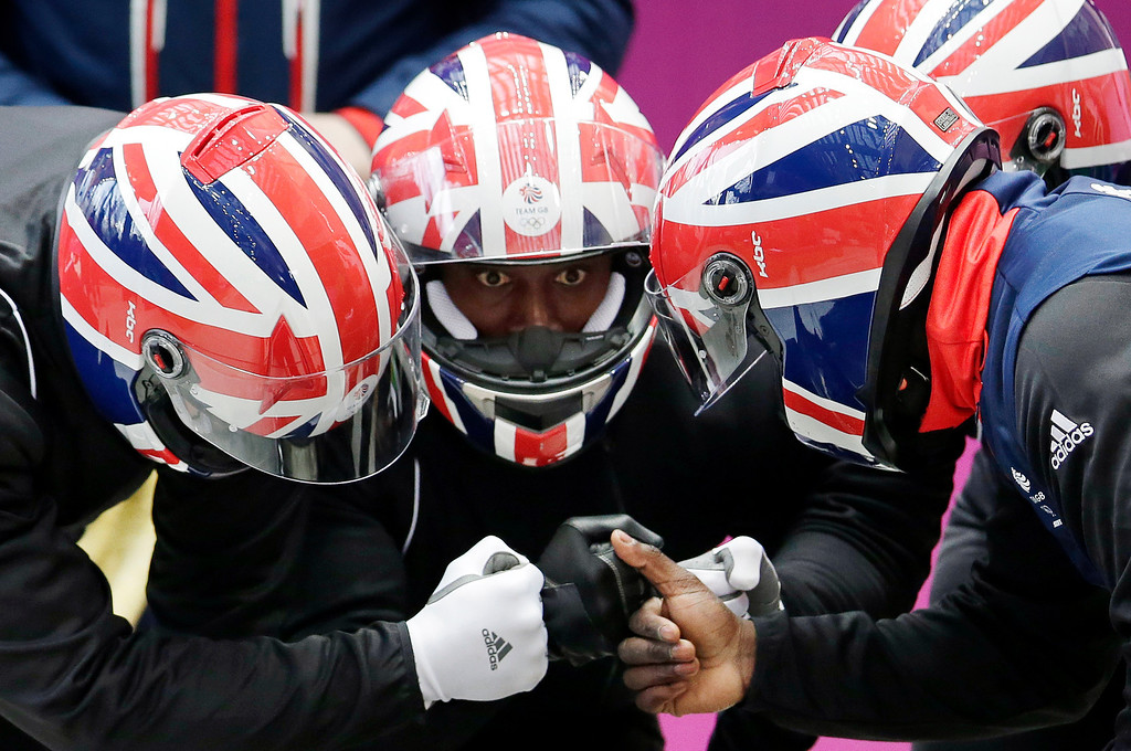 . The team from Britain GBR-2, piloted by Lamin Deen, prepare to start a run during the men\'s four-man bobsled training at the 2014 Winter Olympics, Wednesday, Feb. 19, 2014, in Krasnaya Polyana, Russia. (AP Photo/Michael Sohn)