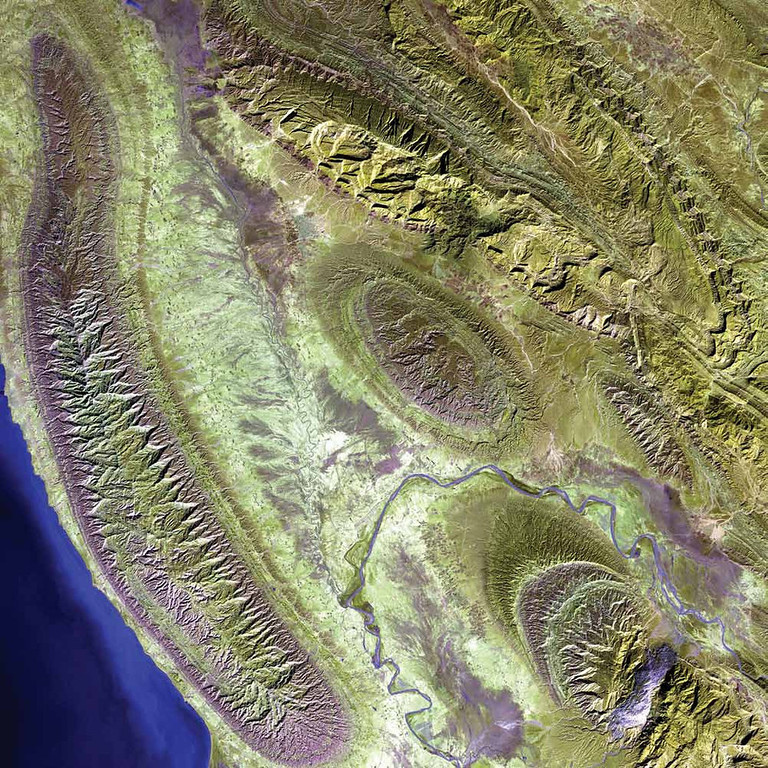 . Zagros Mountains, Iran The Zagros Mountains in southwestern Iran present an impressive landscape of long, linear ridges and valleys. In the lower right corner of this 2000 Landsat 7 image stands a feature of the area�a white-topped salt dome called Kuh-e-Namak, or �mountain of salt� in Farsi. Thick layers of minerals, such as halite (common table salt), typically accumulate in closed basins during alternating wet and dry climatic conditions. Over time, the layers of salt are buried under younger layers of rock. The pressure from overlying rock layers causes the lower-density salt to flow upwards, bending the rock layers above and creating a domelike structure. Near the bottom of the image, the Mand River resembles a lavender ribbon as it winds around the base of Kuh-e-Namak. The city of Konari and several other towns and small villages nestle nearby on the valley floor.   NASA