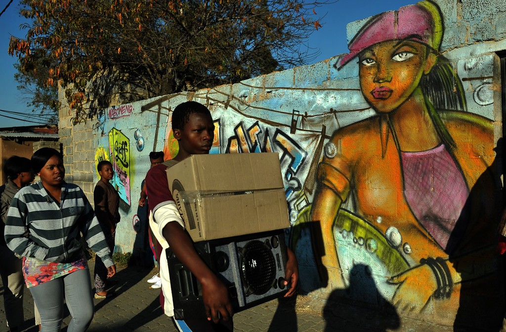 """. People walk past a mural in Alexandra township on June 28, 2013. US President Barack Obama arrived in South Africa on Friday to pay homage to his hero Nelson Mandela, who was said to be showing \""""great improvement\"""" in hospital. ALEXANDER JOE/AFP/Getty Images"""