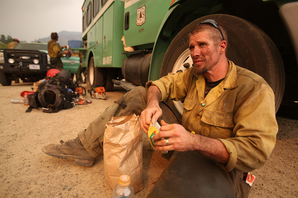 . David Snelling, with Tatanka Hotshots from South Dakota, takes a brief break to eat after working to build defensive lines around homes to protect them from the more than 90,000-acre Elk Complex Fire near Pine, Idaho, on Monday August 12, 2013.    (AP Photo/Times-News, Ashley Smith)