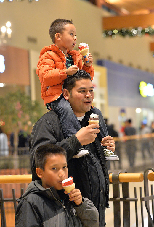 . Aaron Mejia, 3, top, his father Juan and brother Eric, 9, eat ice cream while shopping with their family at FlatIron Crossing mall on Thursday, November 28, 2013. David R. Jennings/Boulder Daily Camera