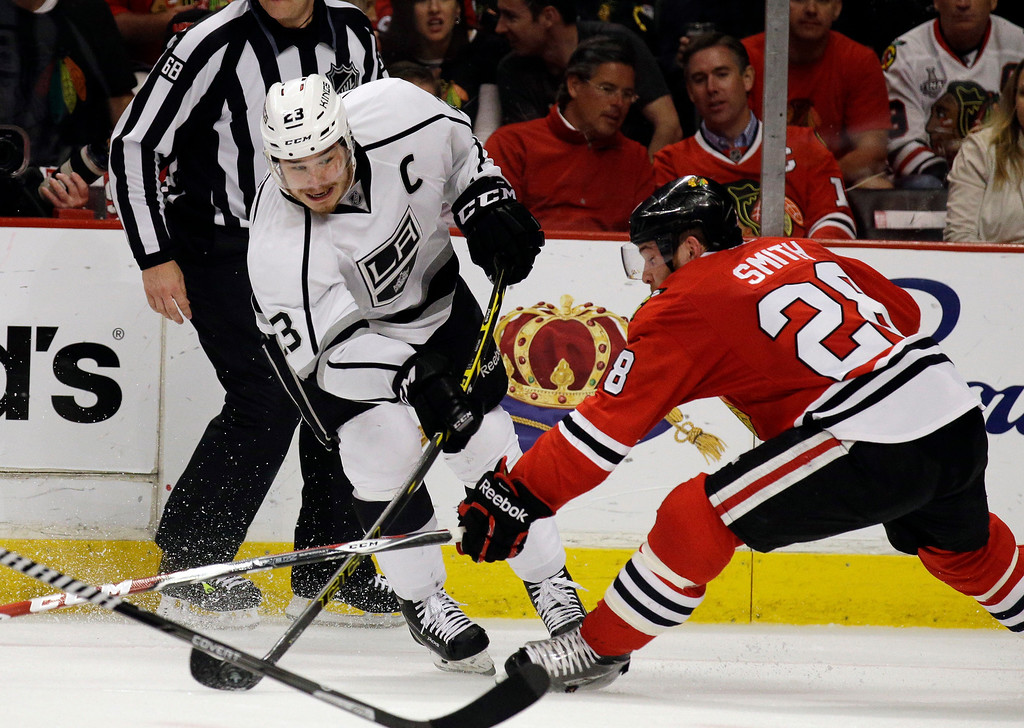 . Los Angeles Kings right wing Dustin Brown (23) shoots against Chicago Blackhawks right wing Ben Smith (28) during the first period in Game 7 of the Western Conference finals in the NHL hockey Stanley Cup playoffs Sunday, June 1, 2014, in Chicago. (AP Photo/Nam Y. Huh)