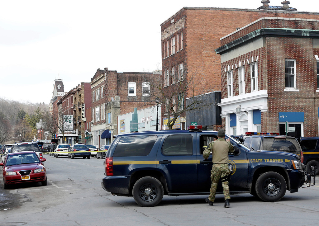 . Law enforcement officers block off Main Street  in Herkimer, N.Y., while searching for a suspect in two shootings that killed four and injured at least  two on, Wednesday, March 13, 2013.  (AP Photo/Mike Groll)