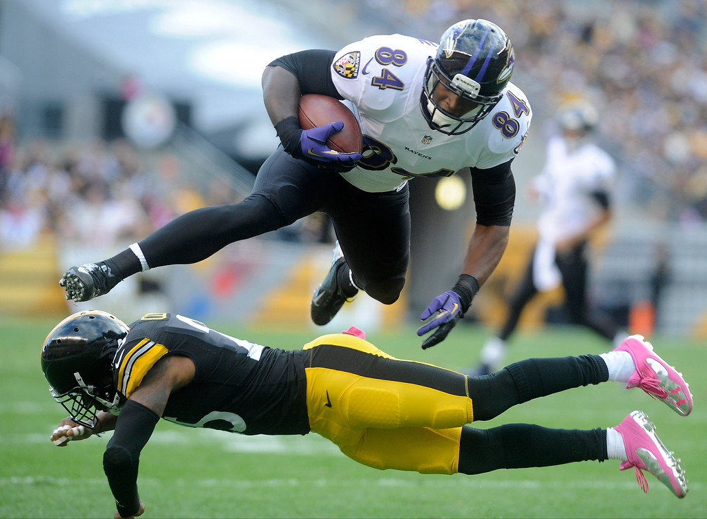 . Ed Dickson # 84 of the Baltimore Ravens leaps over Ryan Clark #25 of the Pittsburgh Steelers during the first quarter at Heinz Field on October 20, 2013 in Pittsburgh, Pennsylvania. (Photo by Vincent Pugliese/Getty Images)