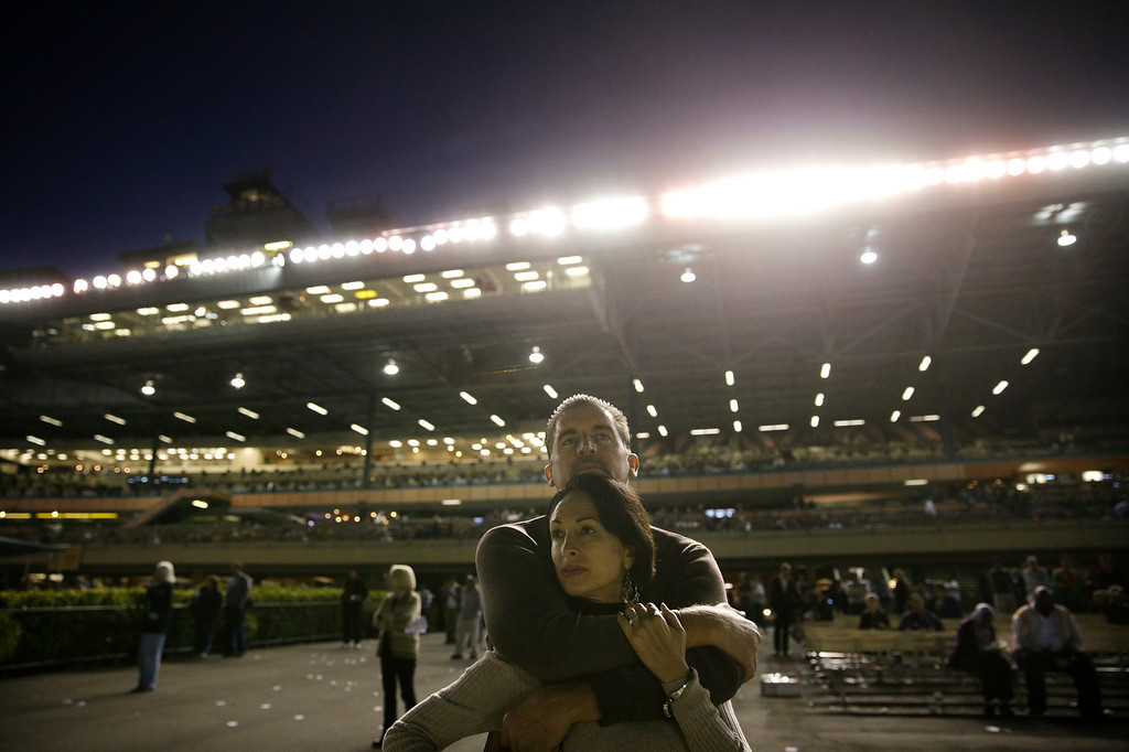 . Gary Carmen and his wife, Tripp, first-time visitors who came to see the track before its closing, hug while watching a horse race at Betfair Hollywood Park on Saturday, Dec. 14, 2013, in Inglewood, Calif. After 75 years of thoroughbred racing, Betfair Hollywood Park is closing for good. The 260-acre track that hosted Seabiscuit and the first Breeders\' Cup in 1984 will be turned into a housing and retail development starting next year. (AP Photo/Jae C. Hong)