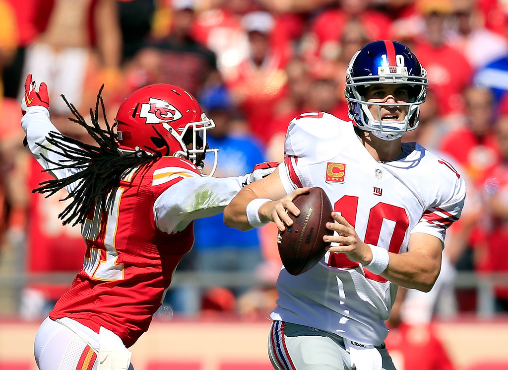. KANSAS CITY, MO - SEPTEMBER 29:  quarterback Eli Manning #10 of the New York Giants scrambles as cornerback Dunta Robinson #21 of the Kansas City Chiefs rushes during the game at Arrowhead Stadium on September 29, 2013 in Kansas City, Missouri.  (Photo by Jamie Squire/Getty Images)