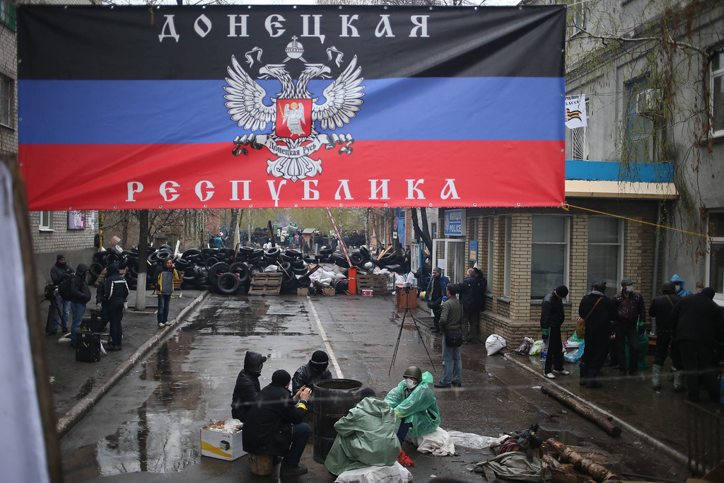 ". Pro-Russian activists gather at a seized police station with a banner reading ""Donetsk Republic\"" in the eastern Ukrainian town of Slovyansk on Sunday, April 13, 2014. Ukrainian special forces exchanged gunfire with a pro-Russia militia in the eastern city Sunday, according to the interior minister, who said one Ukrainian security officer was killed and five others wounded. It was the first reported gunbattle in east Ukraine, where armed pro-Russia men have seized a number of law enforcement buildings in recent days. .(AP Photo/Andrew Chernavsky)"