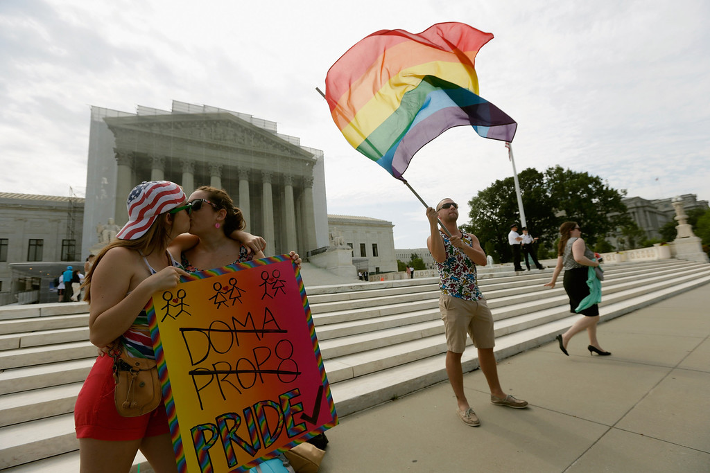. WASHINGTON, DC - JUNE 24:  Gay rights activists Meghan Cleary (L) and Sarah Beth Alcabes from Berkley, CA kiss front of the U.S. Supreme Court building as Vin Testa of DC waves a flag June 24, 2013 in Washington DC. The high court is expected to rule this week on some high profile decisions including California\'s Proposition 8, the controversial ballot initiative that defines marriage as between a man and a woman.  (Photo by Win McNamee/Getty Images)