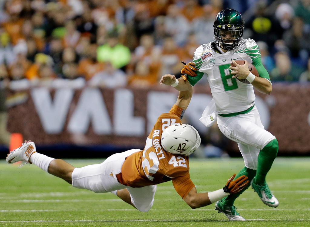 . Oregon\'s Marcus Mariota (8) is pulled down by  Texas\' Caleb Bluiett (42) during the first quarter in the Valero Alamo Bowl NCAA college football game, Monday,  Dec. 30, 2013, in San Antonio. (AP Photo/Eric Gay)