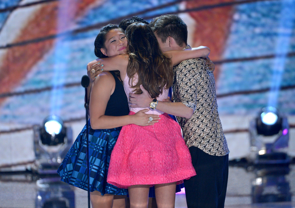 ". The cast of ""Glee\"", from left, Jenna Ushkowitz, Lea Michele and Kevin McHale hug on stage at the Teen Choice Awards at the Gibson Amphitheater on Sunday, Aug. 11, 2013, in Los Angeles. (Photo by John Shearer/Invision/AP)"