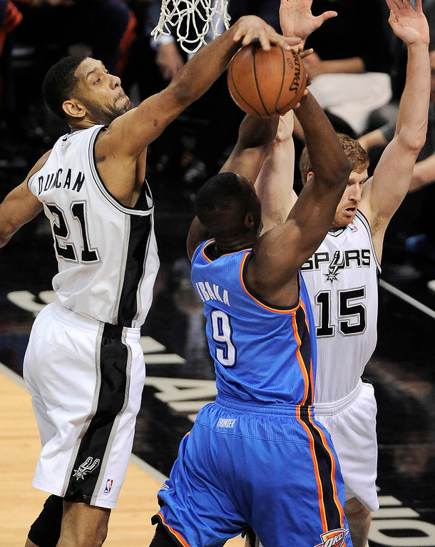 . San Antonio Spurs forward Tim Duncan, left, blocks a shot by Oklahoma City Thunder forward Serge Ibaka (9) as Matt Bonner helps on defense during the first half of Game 5 of the NBA basketball playoffs Western Conference finals, Thursday, May 29, 2014, in San Antonio. (AP Photo/Darren Abate)