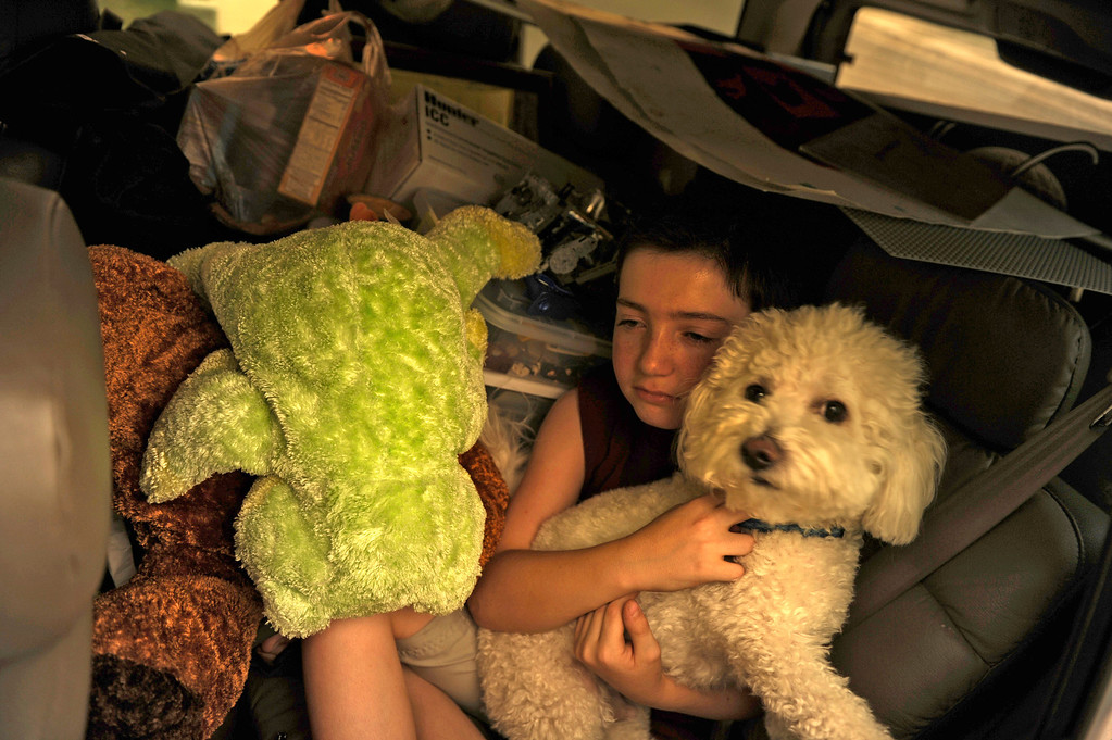 . Taylor Salamon, 11, holds on to his dog as they pile in the back seat, Tuesday, June 26, 2012, as his family rushes to leave their home in the path of Waldo Canyon Fire in Colorado Springs. RJ Sangosti, The Denver Post