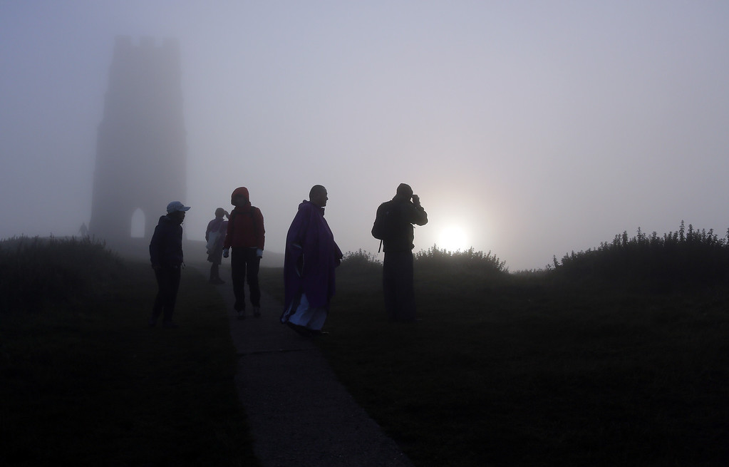 . Visitors to Glastonbury Tor take a photographs of St. Michael\'s Tower, a ruined 14th-century church tower, as the sun rises and begins to clear the early morning mist and fog near the town of Glastonbury on September 4, 2013 in Somerset, England.  (Photo by Matt Cardy/Getty Images)