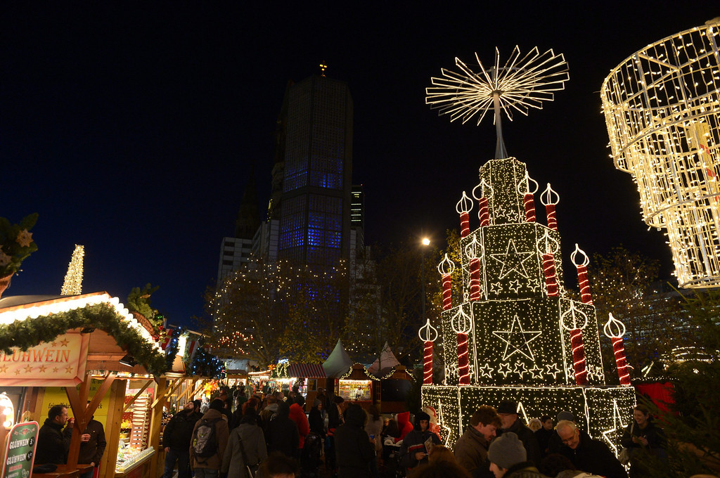 . Visitors walk at the Christmas market in Berlin, Germany, 26 November 2013. In the background is Kaiser Wilhelm Memorial Church. About 170 stand will be open until 01 January 2013.  EPA/Rainer Jensen