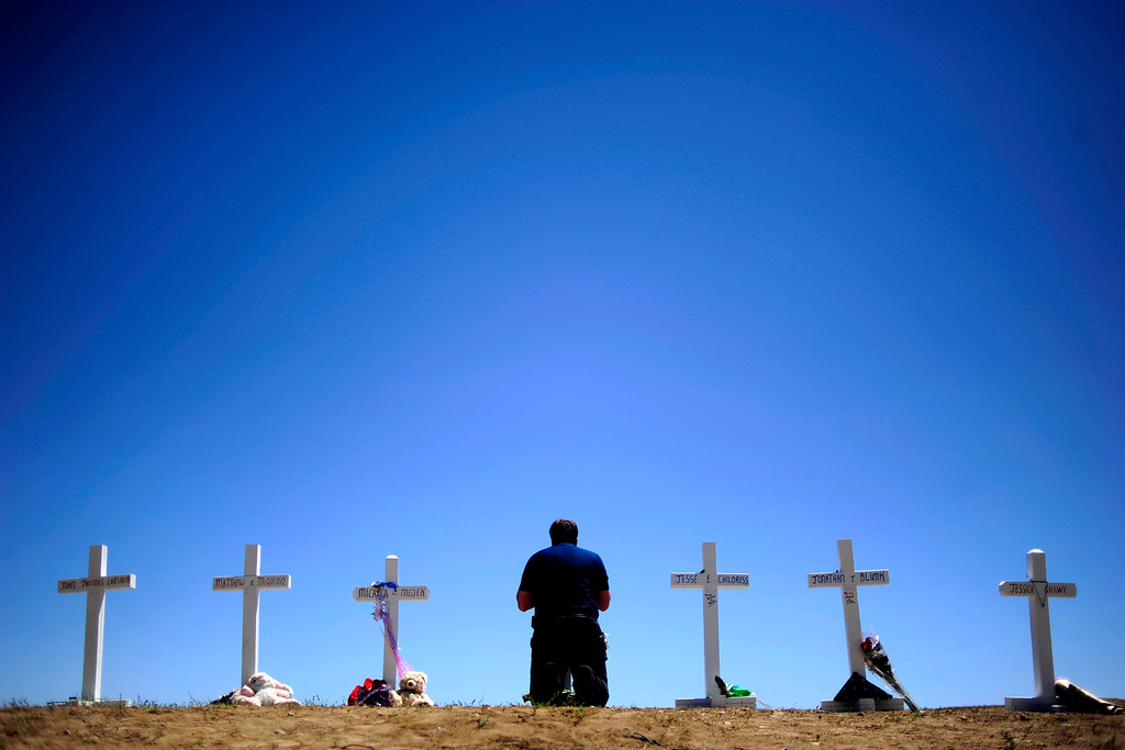 . Travis Hirko kneels at the cross of Alex Sullivan at a memorial for the victims of the Aurora Theater Shooting at the intersection of Sable Boulevard and Centerpoint Drive on Sunday, July 22, 2012. Greg Zanis, an electrician from Aurora, Illinois, travelled across the country to erect 12 crosses on a hill near the theater. He had made the same journey 13 years earlier to Columbine high school. The memorial became the physical center of the community\'s grief. AAron Ontiveroz, The Denver Post