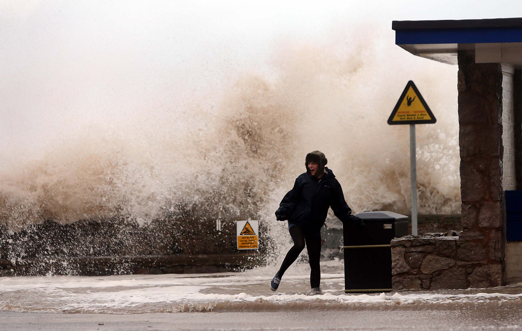 . A woman stands in front of a huge wave on the seafront,  in Rhyl, Wales, Thursday Dec. 5, 2013.   (AP Photo/PA,  Peter Byrne)