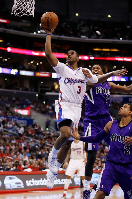 . Los Angeles Clippers guard Chris Paul shoots the ball in front of Sacramento Kings forward Rudy Gay, second right, and Kings guard Ray McCallum, right, during the first half of an NBA basketball game in Los Angeles, Sunday, April 12, 2014. (AP Photo/Danny Moloshok)