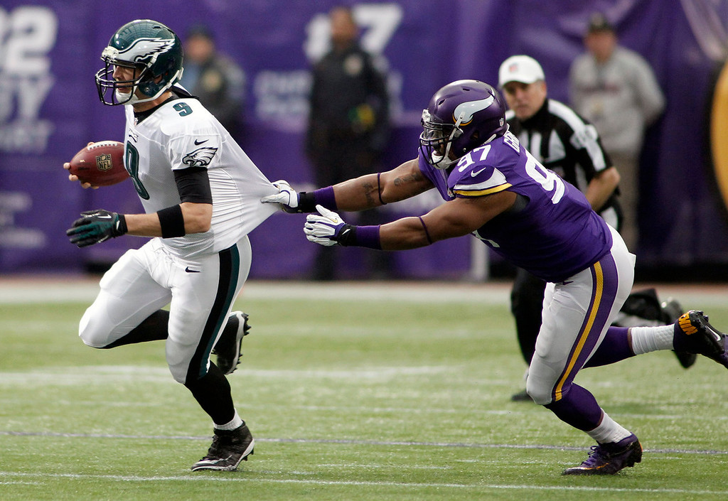 . Philadelphia Eagles quarterback Nick Foles, left, runs from Minnesota Vikings defensive end Everson Griffen during the first half of an NFL football game, Sunday, Dec. 15, 2013, in Minneapolis. (AP Photo/Andy King)