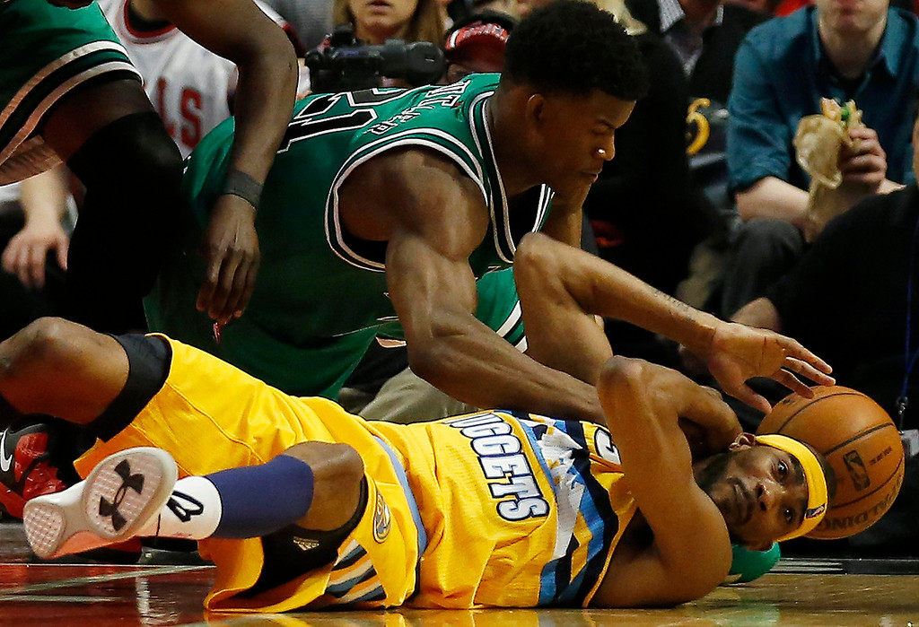 . Chicago Bulls\' Jimmy Butler (top) and Denver Nuggets\' Corey Brewer battle for a loose ball during the second half of their NBA basketball game in Chicago, Illinois March 18, 2013.   REUTERS/Jim Young