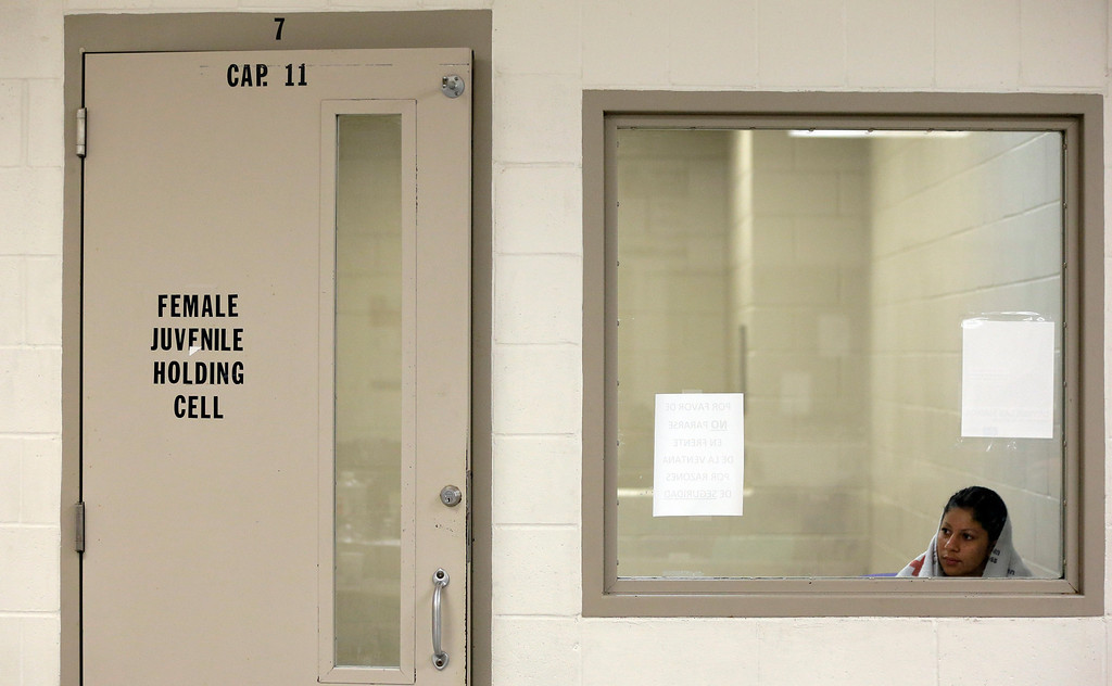 . A detainee sits in a holding cell at a U.S. Customs and Border Protection processing facility, Wednesday, June 18, 2014, in Brownsville,Texas.  (AP Photo/Eric Gay, Pool)
