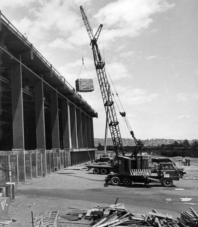 . Crane lifts roofing material to the top of the $5.8 million field house. The in door athletic complex will have a 2,600-seat ice hockey arena, a 6,600-seat basketball arena, and a one-sixth mile track, practice field. 1967. The Denver Post Library Archive  Credit: Denver Post