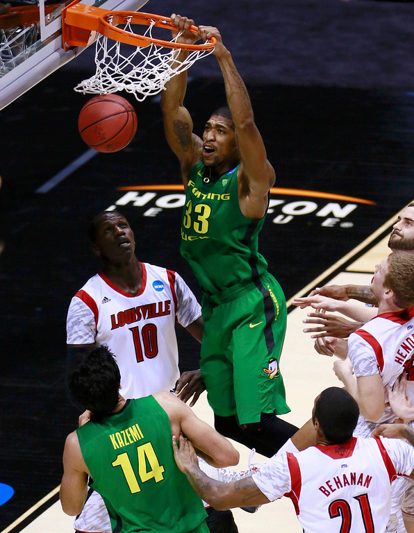 . Oregon Ducks forward Carlos Emory (33) dunks over Louisville Cardinals center Gorgui Dieng (10) during their Midwest Regional NCAA men\'s basketball game in Indianapolis, Indiana, March 29, 2013. REUTERS/Brent Smith