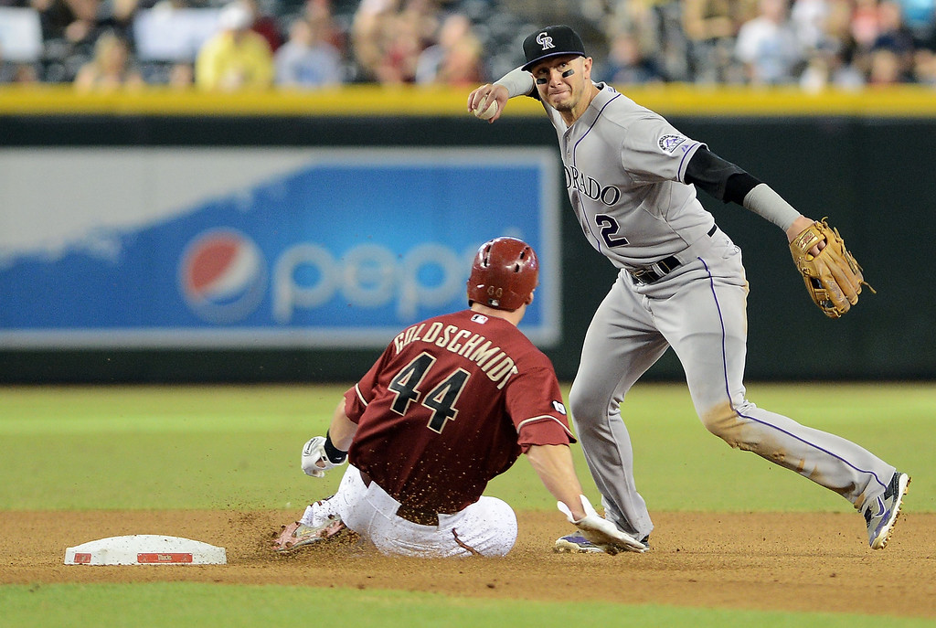 . Infielder Troy Tulowitzki #2 of the Colorado Rockies turns the double play over the sliding Paul Goldschmidt #44 of the Arizona Diamondbacks in the seventh inning at Chase Field on September 15, 2013 in Phoenix, Arizona.  The Diamondbacks defeated the Rockies 8-2.  (Photo by Jennifer Stewart/Getty Images)