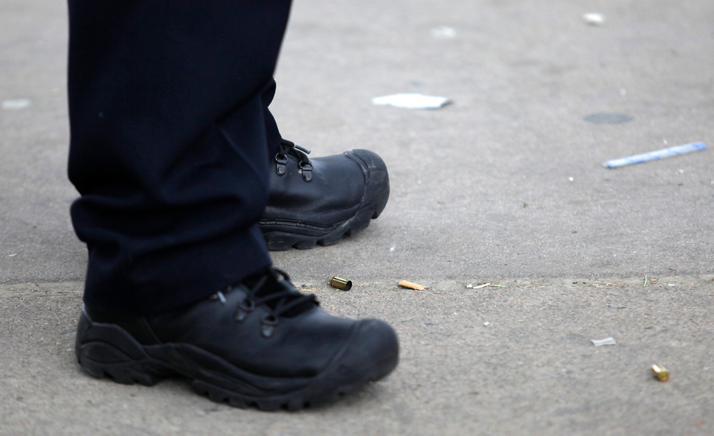 . Denver, CO. - April 20: A Denver Police officer, protects two spent brass rounds on the ground after gunfire interrupted the 4/20 rally in Civic Center park. Two people were shot during Saturday\'s annual 4/20 marijuana rally that drew tens of thousands to Denver\'s Civic Center park. This is the first 4/20 marijuana rally since Colorado voters legalized marijuana use for people 21 and older in November. (Photo By Manuel Martinez, Colorado Media Pro/Special to The Denver Post)