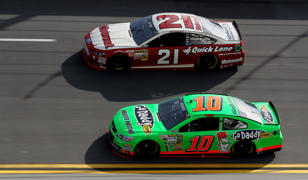 . Danica Patrick, driver of the #10 GoDaddy.com Chevrolet, and Trevor Bayne, driver of the #21 Motorcraft/Quick Lane Tire & Auto Center Ford, race side by side during the NASCAR Sprint Cup Series Budweiser Duel 1 at Daytona International Speedway on February 21, 2013 in Daytona Beach, Florida.  (Photo by Todd Warshaw/Getty Images)