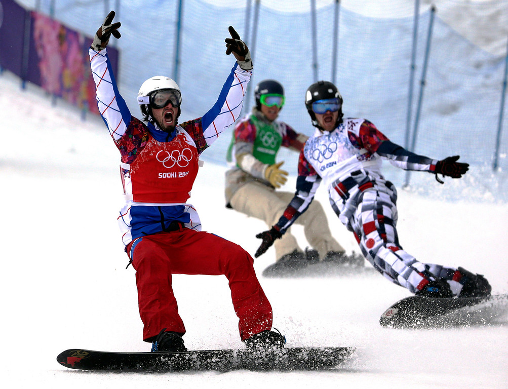 . France\'s Pierre Vaultier, left, celebrates taking the gold medal ahead of silver medalist Nikolai Olyunin of Russia, right, and bronze medalist Alex Deibold of the United States in the men\'s snowboard cross final at the Rosa Khutor Extreme Park, at the 2014 Winter Olympics, Tuesday, Feb. 18, 2014, in Krasnaya Polyana, Russia. (AP Photo/Andy Wong)