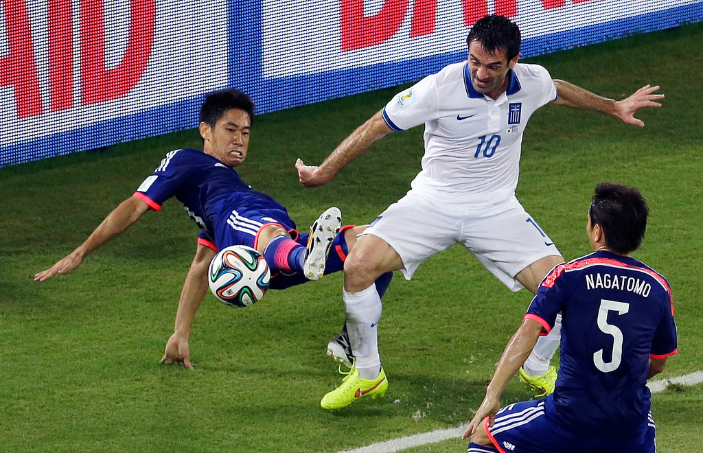 . Japan\'s Shinji Kagawa, left, and Greece\'s Giorgos Karagounis challenge for the ball during the group C World Cup soccer match between Japan and Greece at the Arena das Dunas in Natal, Brazil, Thursday, June 19, 2014. (AP Photo/Hassan Ammar)