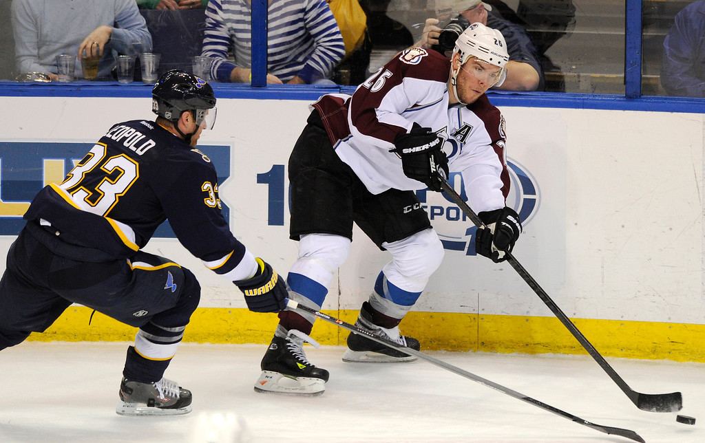 . Colorado Avalanche\'s Paul Stastny (26) passes around St. Louis Blues\' Jordan Leopold (33) during the second period of an NHL hockey game, Saturday, April 5, 2014, in St. Louis. (AP Photo/Bill Boyce)