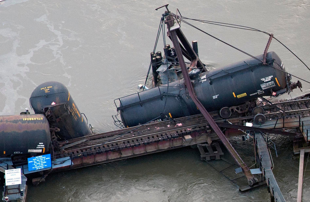 ". Derailed freight train cars, one marked ""vinyl chloride\"", lay in water in Paulsboro, N.J., Friday, Nov. 30, 2012. People in three southern New Jersey towns were told Friday to stay inside after the freight train derailed and several tanker cars carrying hazardous materials toppled from a bridge and into a creek. (AP Photo/Cliff Owen)"