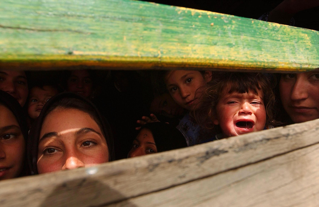 . A family tries to leave the besieged Iraqi city of Basra March 31, 2003 in the back of a truck near a British manned bridge that had become a demarcation line. Basra, Iraq\'s second largest city, had been declared a military target as Saddam Hussein loyalists took up positions in the city, stalling any coalition entry. (Photo by Spencer Platt/Getty Images)