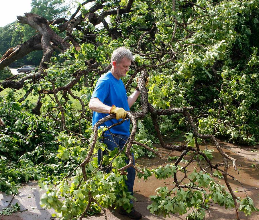 . Brad Avery of Edmond, Oklahoma, clears downed trees from his driveway after a tornado swept through the eastern part of Edmond, Oklahoma May 19, 2013.  A tornado half a mile wide struck near Oklahoma City on Sunday, part of a massive storm front that hammered the central United States. News reports said at least one person had died. REUTERS/Bill Waugh