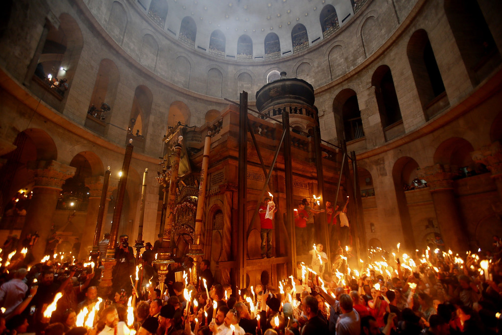 . Christian Orthodox worshippers hold up candles lit from the \'Holy Fire\' as thousands gather in the Church of the Holy Sepulchre in Jerusalem\'s old city on April 19, 2014 during the \'Holy Fire\' ceremony on the eve of the Orthodox Easter.  AFP PHOTO/GALI  TIBBON/AFP/Getty Images