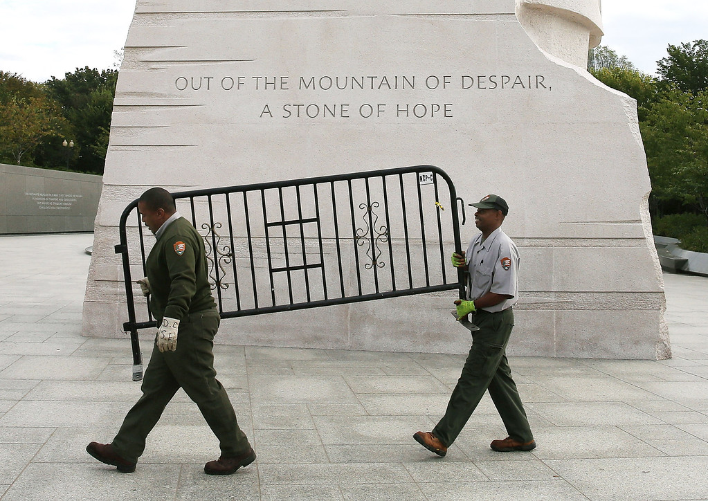 . U.S. Park Service workers carry a barricade that was used to close the Martin Luther King Memorial on the morning after a bipartisan bill was passed by the House and the Senate to reopen the government and raise the debt limit, on October 17, 2013 in Washington, DC. President Obama signed the bill into law, that will fund the government until January 15, 2014 and allow the government to pay bills until February 7, 2014.  (Photo by Mark Wilson/Getty Images)