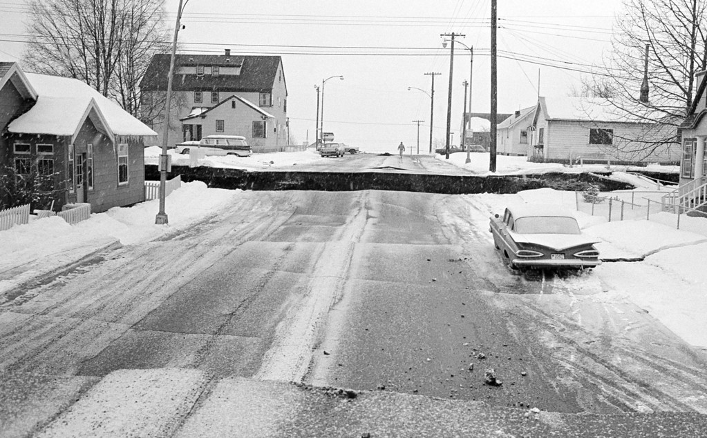 . In this March 28, 1964 file photo, a huge crevasse is seen in the middle of a street in Anchorage, Alaska in the aftermath of an earthquake.  One section of the street is several feet higher than the other. (AP Photo/File)