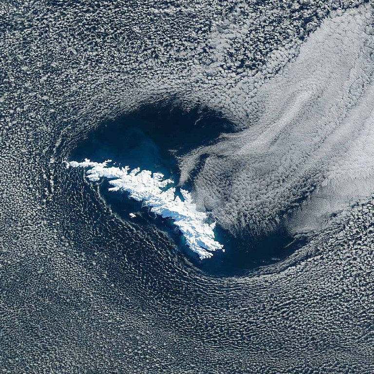. South Georgia Island, South Atlantic Ocean Located in the South Atlantic Ocean due east of Argentina�s southernmost tip, South Georgia Island is entirely covered by snow and ice in this Terra image from 2002. The island is some 170 kilometers long, with a rugged terrain and 11 mountain peaks more than 2,000 meters high. Many boundary layer cumulus clouds fill the atmosphere surrounding the island. The sinewy patterns snaking across the cloud bank (upper left corner) indicate open-cell convection. The island appears to be creating a wake of thicker marine stratocumulus clouds flowing away from its northeast shore. All around the island, phytoplankton appear to be in bloom, giving the deep-blue South Atlantic waters a lighter, more turquoise hue. Sir Ernest Shackleton stopped on South Georgia Island twice, once in 1914 and again in 1915, as part of the Imperial Trans-Antarctic Expedition he led on the ship Endurance. With no permanent human inhabitants, South Georgia Island is now a wildlife sanctuary and home to seals, reindeer, and sea and land birds.   NASA
