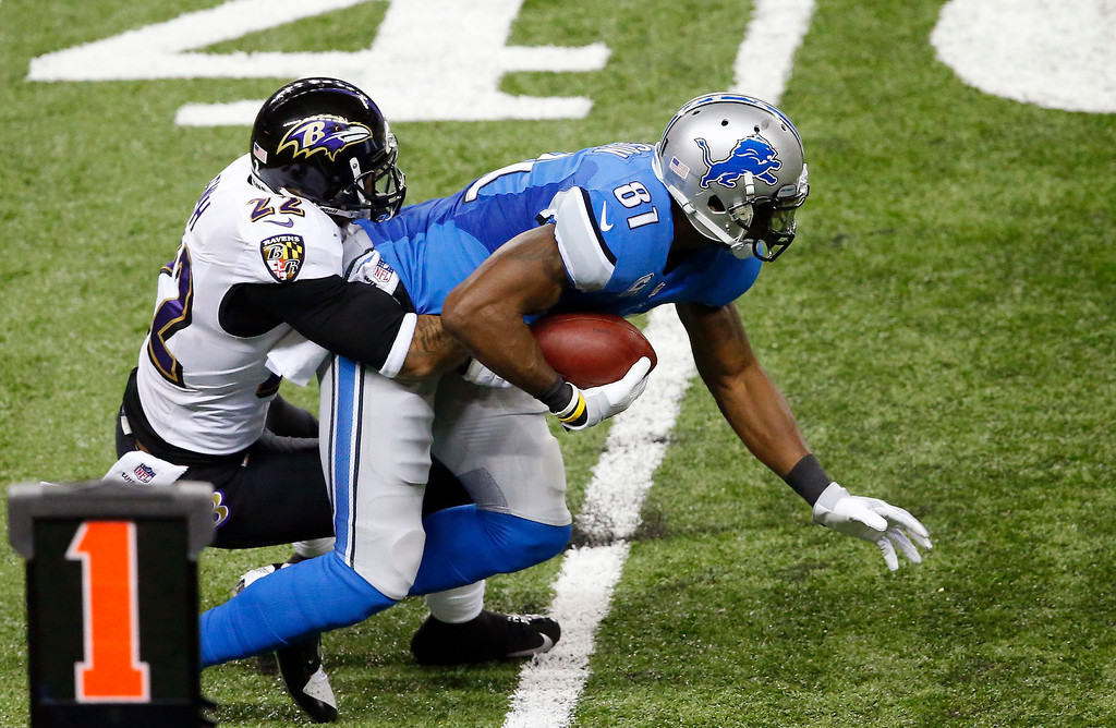 . Detroit Lions wide receiver Calvin Johnson (81) is stopped by Baltimore Ravens cornerback Jimmy Smith (22) during the first half of an NFL football game in Detroit, Monday, Dec. 16, 2013. (AP Photo/Paul Sancya)