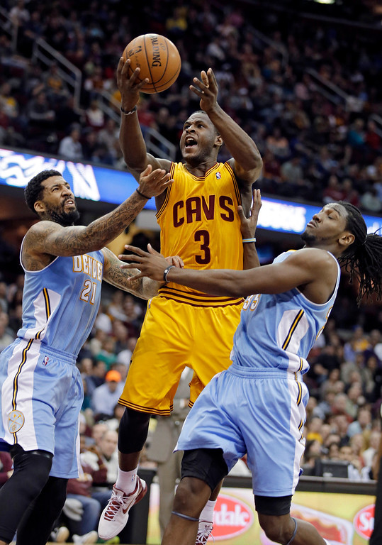 . Cleveland Cavaliers\' Dion Waiters (3) shoots between Denver Nuggets\' Wilson Chandler, left, and Kenneth Faried in the second quarter of an NBA basketball game Saturday, Feb. 9, 2013, in Cleveland. (AP Photo/Mark Duncan)